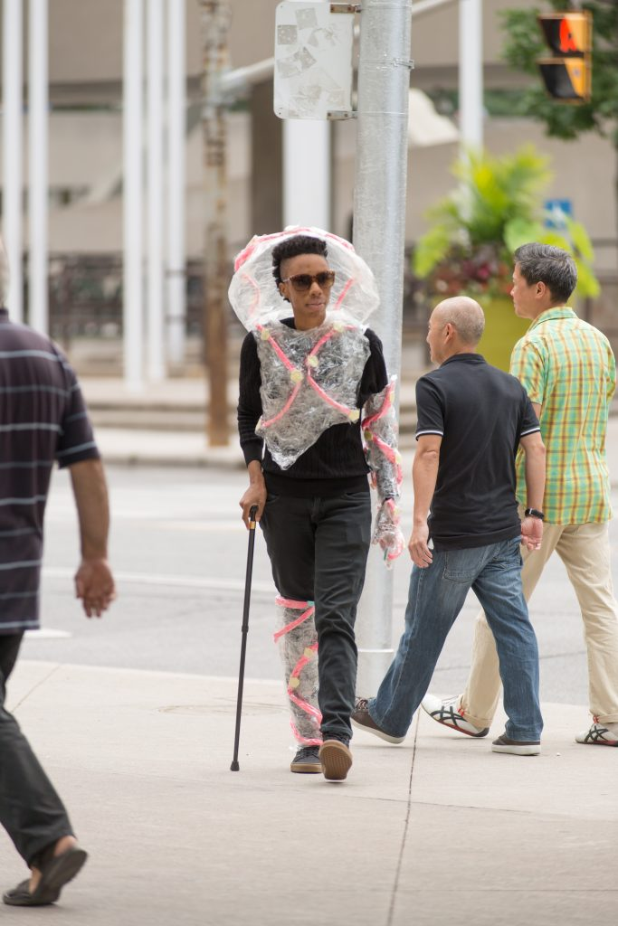 Artist Lynx Sainte Marie walking down street with their cane and wearing a futuristic plastic suit