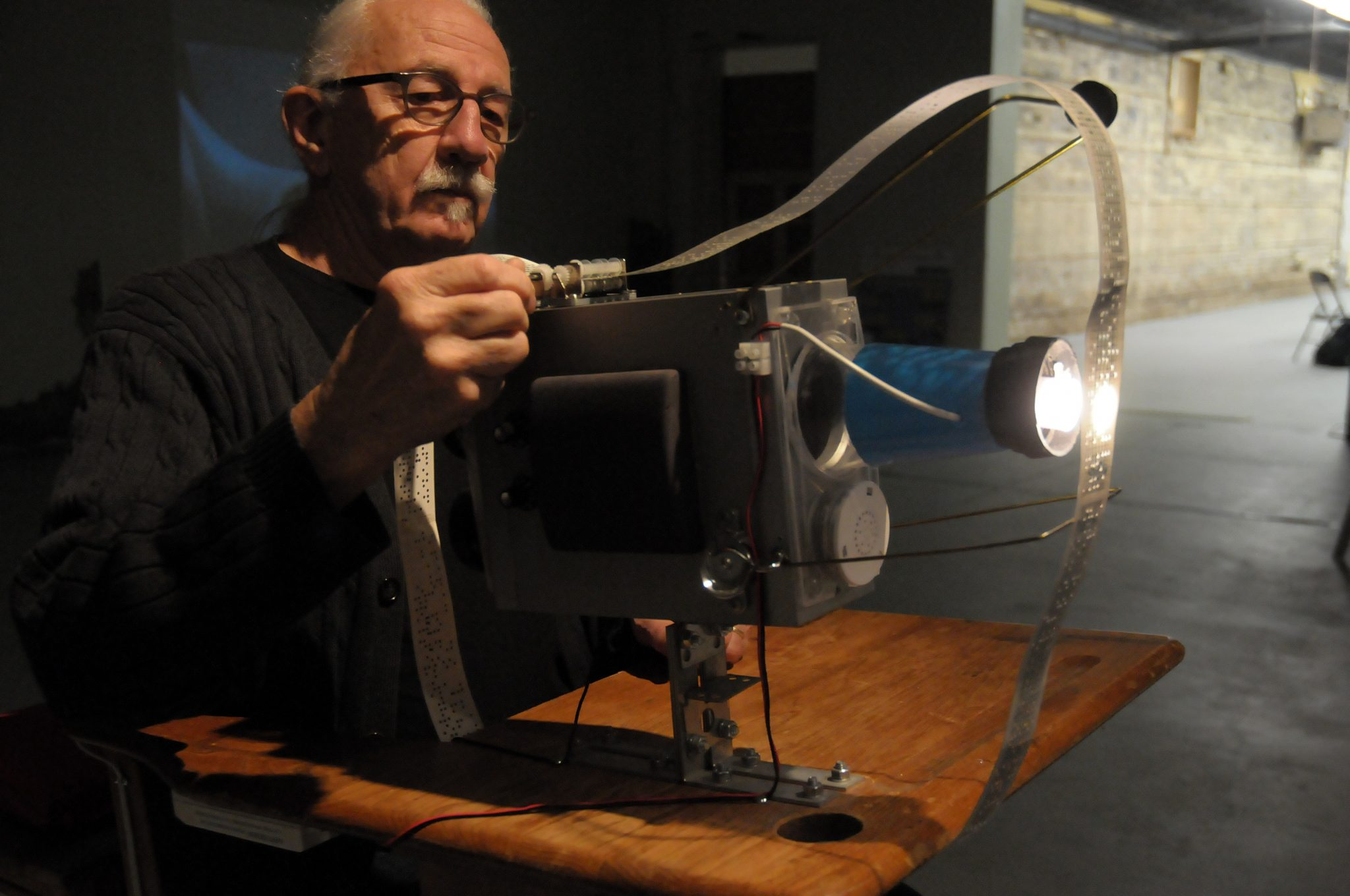 The image is a colour photograph of David Bobier, with his hair pulled back in a ponytail, wearing a black sweater and glasses. His right hand is extended and adjusting a Vibro-projector.