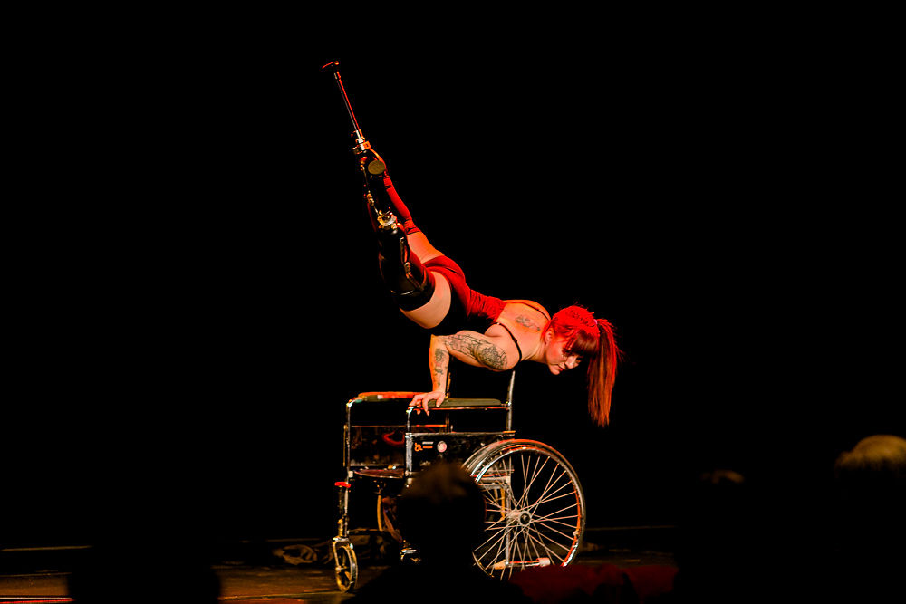 Performer with prosthetics doing a hand stand on wheelchair