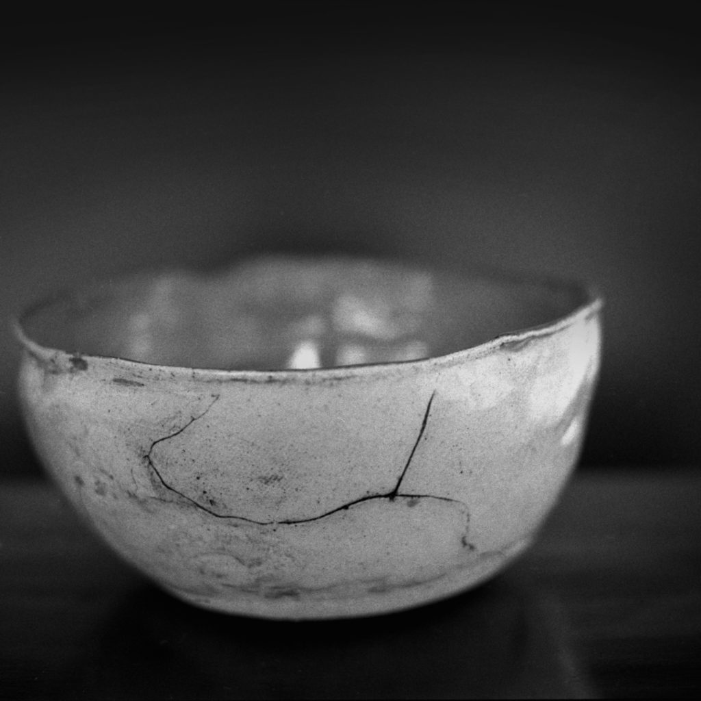 Black and white photo of ceramic bowl with cracks in the glaze