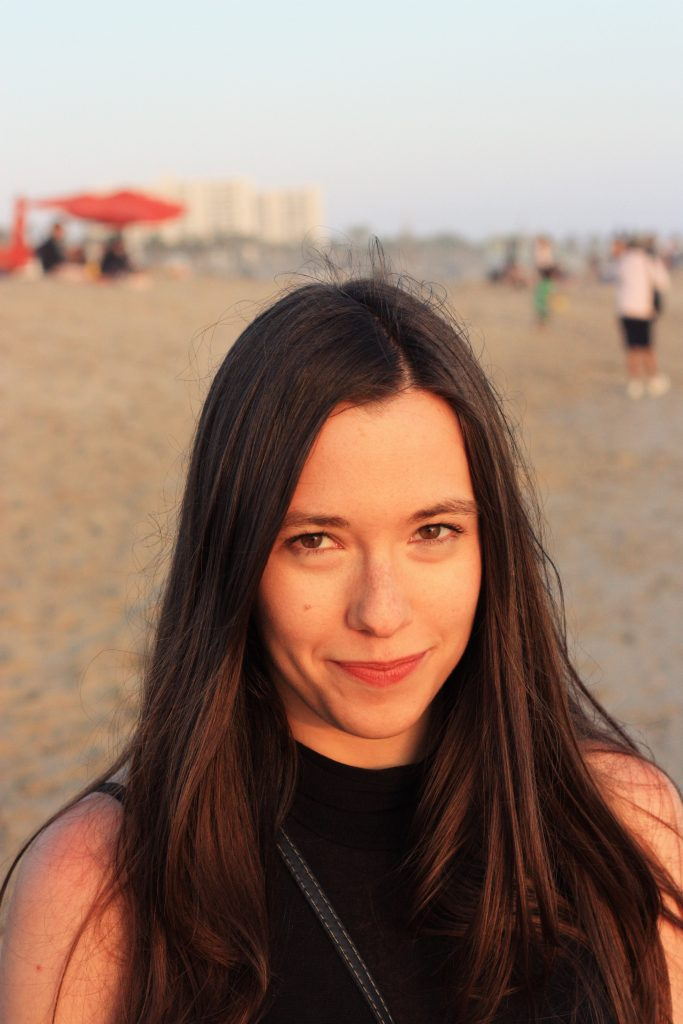 A portrait of Kayla Besse. She is on Santa Monica beach, looking straight at the camera with a close-mouthed smile. She has long brunette hair and is wearing a black sleeveless top.