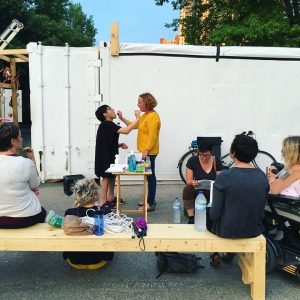 Two people performing outside in front of a shipping container for small group of people.