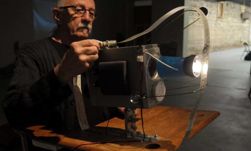 Artist David Bobier standing behind light projector