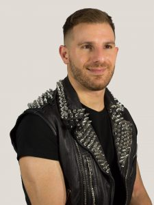 A portrait of Ben Barry. He is looking off to the right of the frame and wearing a studded black leather vest.