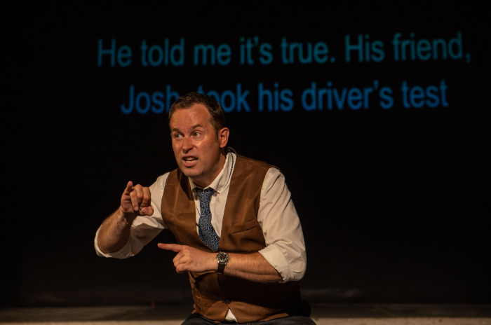 "Chris Dodd performing Deafy at the SummerWorks Performance Festival. Chris wears a white shirt, tan vest and blue tie and is signing animatedly to the audience. Surtitles displayed behind him read ""He told me it's true. His friend, Josh, took the driver's test."""