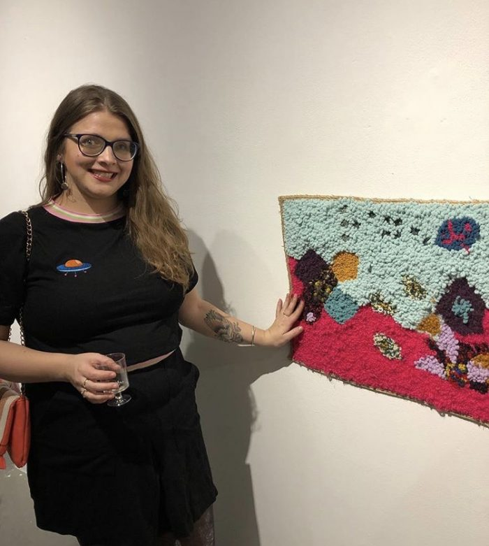 A photo of Jessica standing beside and touching her artwork in a gallery. A tactile rug in shades of pink, blue, purple, and yellow hangs on the wall. Jessica is wearing all black and smiling. She has long hair and glasses.