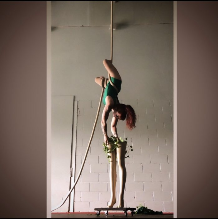A photo of Erin hanging upside down in the air on a single rope that is suspended from the ceiling.