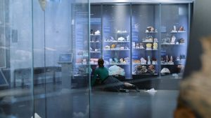 Still image taken from a video. A person is reclined in front of a large glass display filled with gems and minerals.