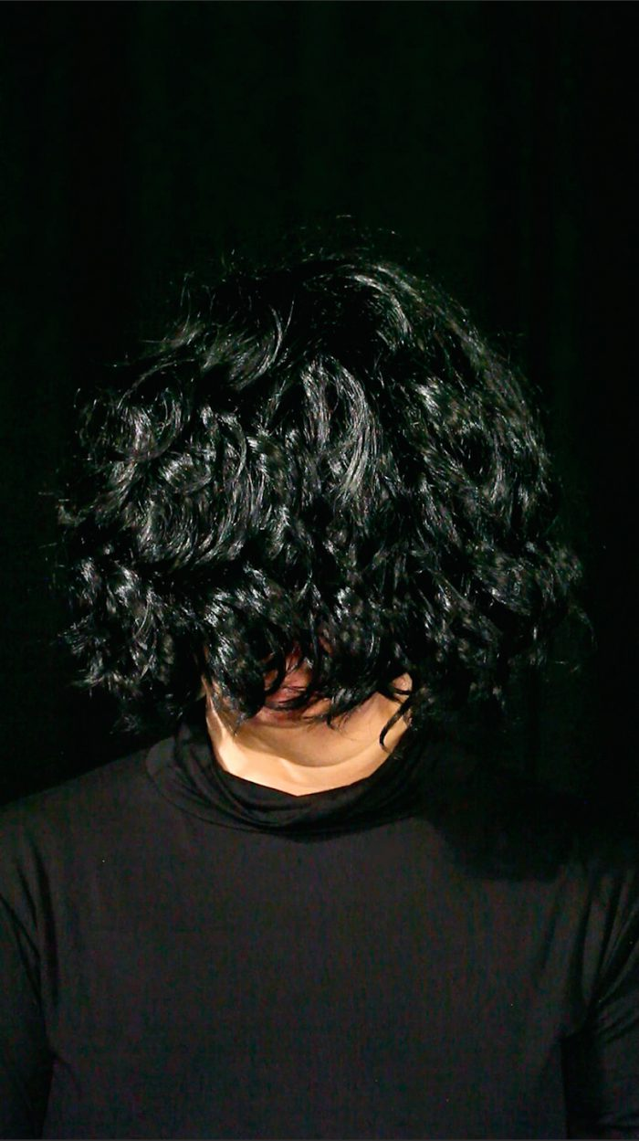 Head and shoulder shot of a woman dressed in a black polo neck sweater and wearing a black wig over her face against a black background. Only her neck and chin are visible.
