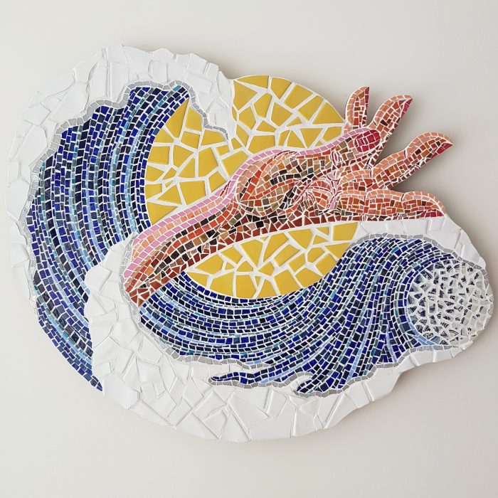 "Photo of commissioned artwork ""All You Can Hold."" It is a wide oval shaped mosaic against a white wall."