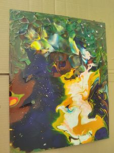 A photo of one of Lev's abstract resin paintings. It primarily has shades of green, blue, and yellow.