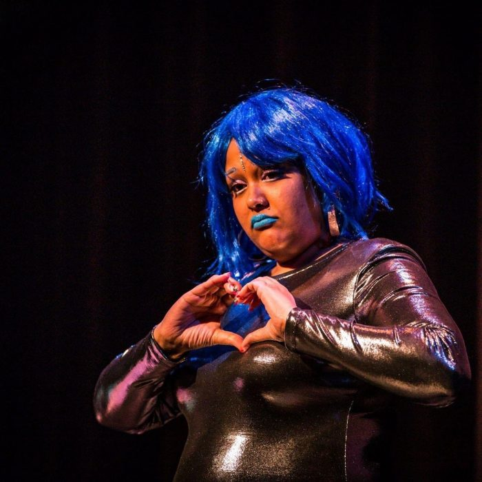 A photo of Gaitrie wearing a blue wig and blue lipstick. She is wearing a metallic bodysuit and signing.