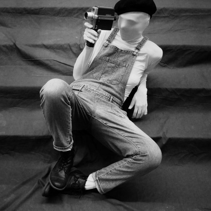 A black and white photo of a performer dressed as the Ubermarionette wearing a morph suit -which covers all visible skin.They are sitting casually leaning back on a flight of stairs. They are wearing light coloured overalls, a black beret and holding a Super8 video camera to their right eye.