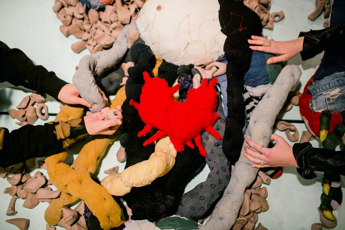 Two people reach out to touch Big Softie's guts, which are soft and dimpled and made from stuffed knee socks and nylon stockings, and examine the Unidentified Remains that are scattered amongst them. At the centre of it all lies Big Softie's heart, a red patchwork soft sculpture with tendrils extending outward.
